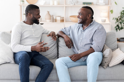 Adult Son And Senior Father Talking While Relaxing On Couch At Home