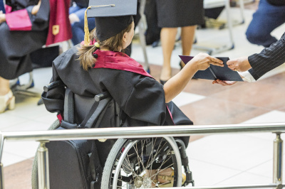 student in wheelchair receives a diploma from a university. disabled girl with a diploma from school and university.