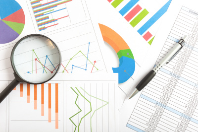 magnifying glass over reports and data